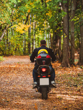 Biker on a motorcycle rides along a forest road with a dog in a backpack on his back. Standard-Bild - 157290859