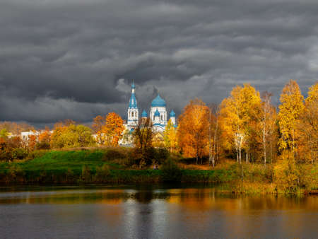 White Cathedral in the distance surrounded by golden autumn trees. Gatchina old city.