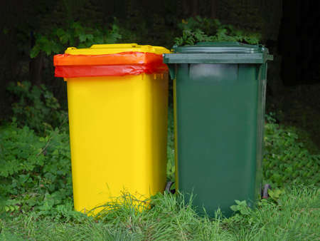 Multi-colored containers for separate garbage collection in a green place.