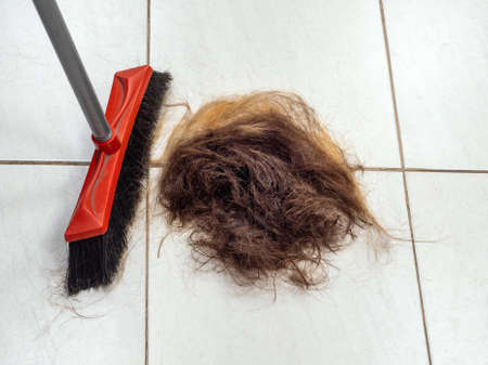 A pile of cut hair on the barber shop floor next to a broom. Standard-Bild - 157321406