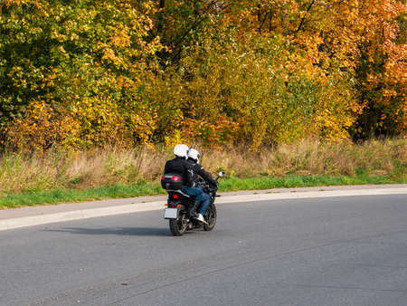 A couple of bikers on the same motorcycle rides on the autumn highway. Standard-Bild - 157397286