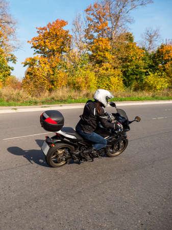 Motorcyclist in motion. Woman biker on a black motorcycle in traffic on a rural autumn road. Standard-Bild - 157529899