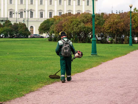 Lawn mower from the back at work. City service, maintenance of the city lawn in the Park. Saint Petersburg. Standard-Bild