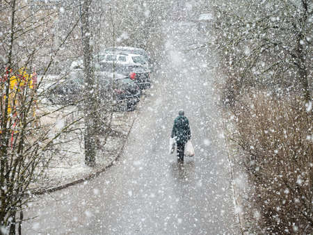 People with bags in his hands under a heavy snowfall is walking down the street. Standard-Bild