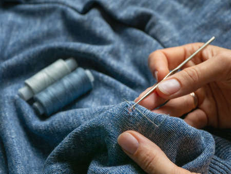 A hole in the clothing. Restoration of a knitted sweater Standard-Bild