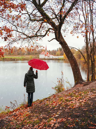 Woman in a dark coat and a red umbrella looks into the distance in a snowy and rainy autumn. 版權商用圖片