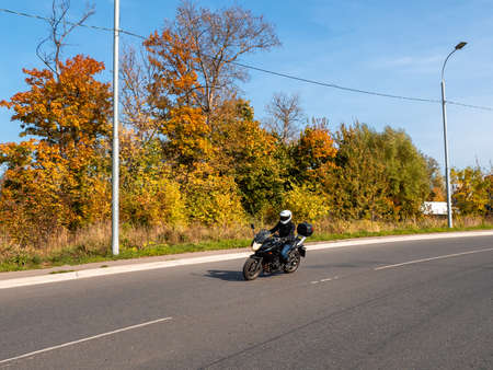 Motorcyclist in motion. Woman biker on a black motorcycle in traffic on a rural autumn road. 免版税图像