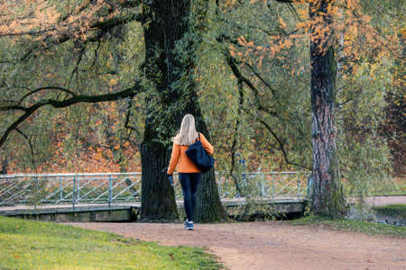 Beautiful blonde in an orange jacket is walking along an autumn alley. The view from the back 版權商用圖片