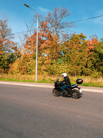 Motorcyclist in motion. Biker on a black motorcycle in traffic on a rural autumn road. Standard-Bild - 157652437