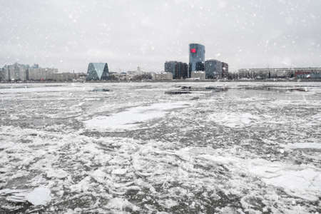 Spring ice drift on the river. Ice on the Neva river in St. Petersburg against the background of urban coastal architecture.