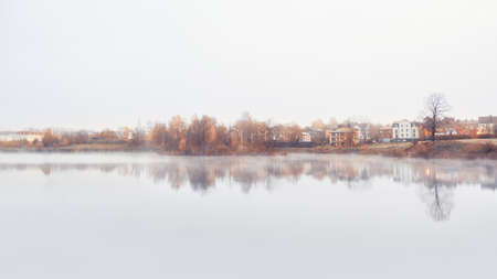Panorama of a misty morning minimalistic landscape with a line of cottages and trees by the water in autumn
