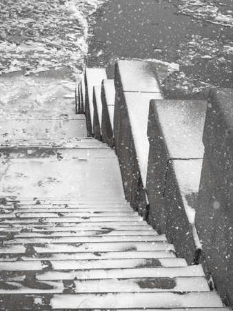 Granite stairs to the frozen river. Ice drift on the river. 版權商用圖片
