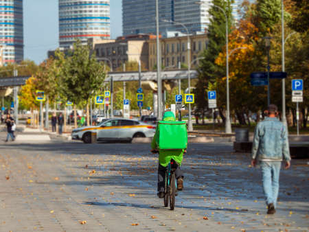 Food delivery. A cyclist delivers food on the autumn street in Moscow