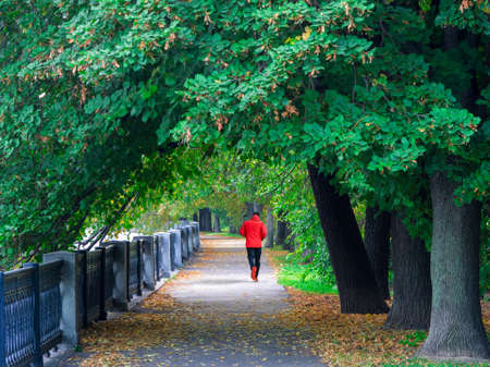 A man in a red sports windbreaker runs down a deserted street early in the morning. Morning fitness run on the embankment in Moscow