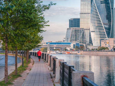 Morning fitness run on the embankment in Moscow. A man in a red sports windbreaker runs down a deserted street early in the morning.
