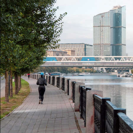 Morning fitness run on the embankment in Moscow. A woman runs down the street in the early morning 版權商用圖片