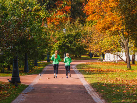 Fitness jog. Two girls jog in an autumn park together.