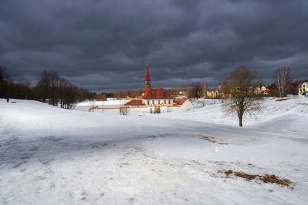 Sanny spring view of the old palace. White snowy landscape with old Maltese palace in beautiful natural landscape. Gatchina. Russia. Редакционное