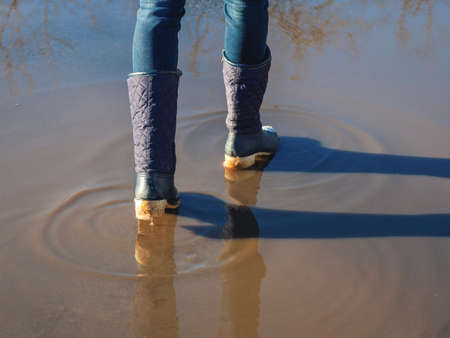 Ice-crusted ground, a woman walking on a slippery street, spring weather. Icy conditions