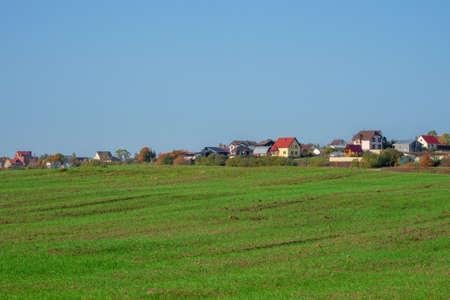 Dacha village on the horizon across the autumn field. Panoramic view. Фото со стока