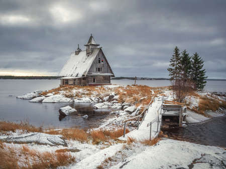 Dramatic landscape with authentic cinematic house on the shore in the Russian village Rabocheostrovsk. A wooden chapel built for the filming of the film.