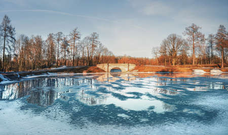 Panorama of the spring Russian park in Gatchina. Karpin pond is covered with puddles and ice.
