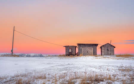 Minimalist landscape. Wooden fish smokehouses in authentic village of Teriberka. Kola Peninsula. Russia. Фото со стока