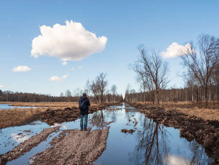 Spring landscape. A road flooded by a flood. A man stands by a large puddle.