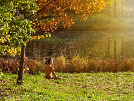A yogi man practices yoga meditation under an autumn tree in a park.