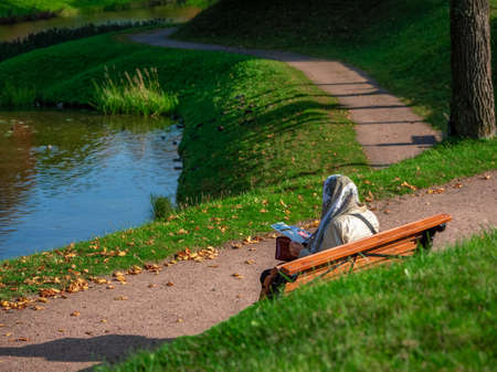 A woman in a headscarf is sitting on a bench in an autumn park and leafing through a magazine. Outdoor recreation.