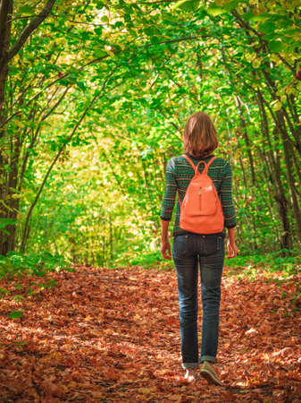 Woman tourist with backpack on dark autumn forest road under arch of trees covering the sky. Фото со стока - 167312865