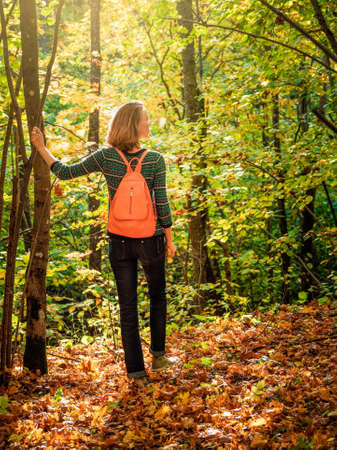 Woman tourist with backpack on dark autumn forest road under arch of trees covering the sky.