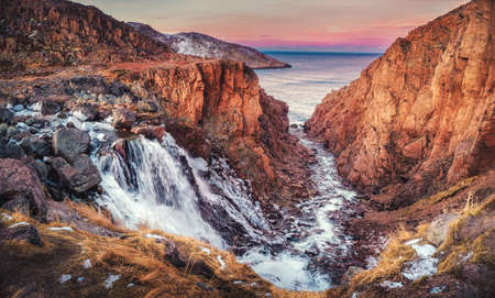 Picturesque waterfall of the Small Battery Lake on the Kola Peninsula, Teriberka. Russia.