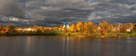 Wide panoramic view the village before the storm. White Cathedral in the distance surrounded by golden autumn trees. Gatchina old city. Фото со стока