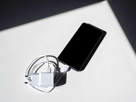 A black smartphone with a charging wire on a white table with shadows. Top view.