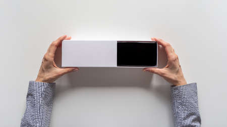 Unpacking a new smartphone on a white table. Female hands holding modern smartphone with blank screen. Online shopping concept. Top view.
