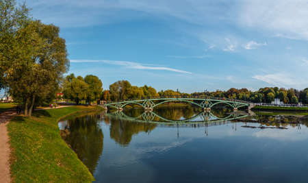 A round fragment of the city river embankment with a large tree branch in autumn Standard-Bild