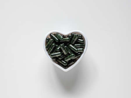 Green chlorella pills. Spirulina capsules in bowl on white background. Top view, copy space.