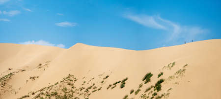 A wide panorama of a large dune with a small silhouette of people walking on it against the blue sky.