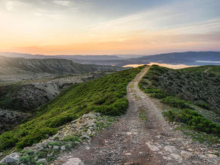 Walking and hiking trails in the mountain range in the early morning. Hike up a narrow mountain path with a stunning view of the vast green valley. Standard-Bild