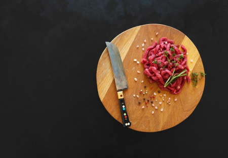 Sliced raw meat on a wooden board. Preparation of beef Stroganoff.