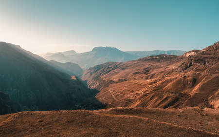 Soft focus. Rocky mountains and the light of the sun in the morning. Sunset view of winding road in high mountain pass. Dagestan. Toning.