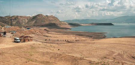 A group of tourists goes to get into the boats. Remote view. Chirkeyskoe reservoir, Dagestan.
