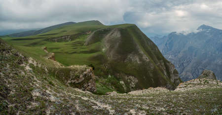 Beautiful panoramic landscape on the rainy high plateau. Rocky ledge stretching into the distance against the background of green textured mountains. Фото со стока