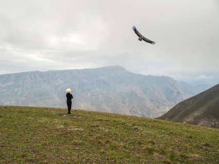 A horseman in a white cap and a flying eagle on the background of high mountains.