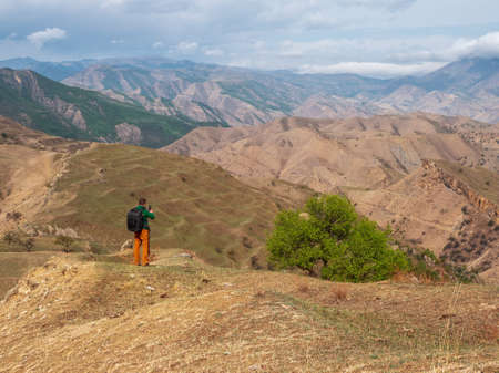 Male tourist with a backpack with a smartphone takes pictures of a beautiful mountain landscape.