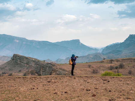 Photographer with a large camera takes pictures of a beautiful mountain landscape.