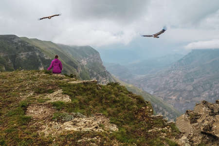 A woman with a camera captures the flight of an eagle in the mountains. Фото со стока