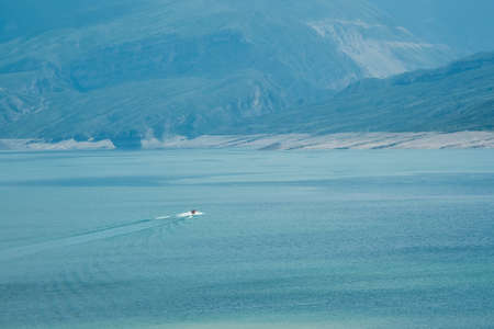 Soft focus. Small power boat on turquoise lagoon among high mountains in the background. Dagestan. Фото со стока