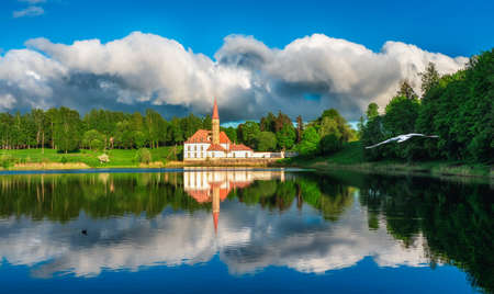 Bright beautiful panoramic spring landscape with peaceful lake, dramatic sky and a old white Maltese castle. Gatchina. Russia.